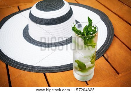 Glass of water with ice and mint and summer hat. Selective focus on glass