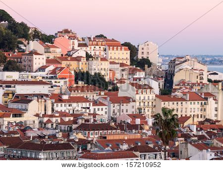 Cityscape of Lisbon Portugal seen from Miradouro Sao Pedro de Alcantara at sunset.
