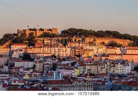 Cityscape of Lisbon Portugal with the Sao Jorge Castle seen from Miradouro Sao Pedro de Alcantara at sunset.