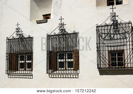 Three windows with an iron grates with Christian cross and wooden shutters. Engadine Switzerland Europe