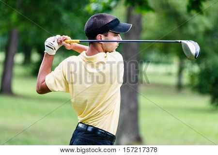 Golfer teeing off with driver, toned image