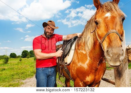 Portrait of happy young man in cowboy hat saddling beautiful horse at the farm