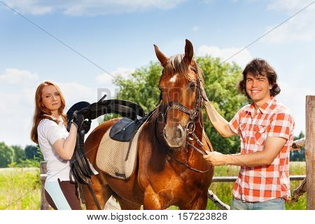 Young man holding bay horse by the bridle while young woman saddling it, standing next to the enclosure fence