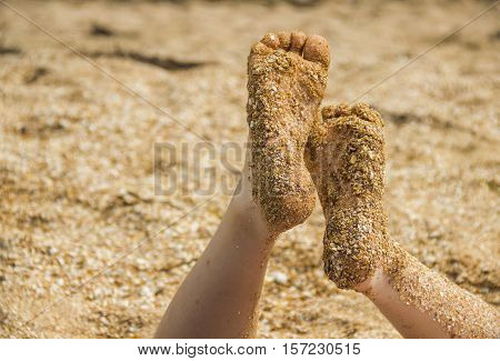 feet of young sunburnt girl in the sand and sea-shells