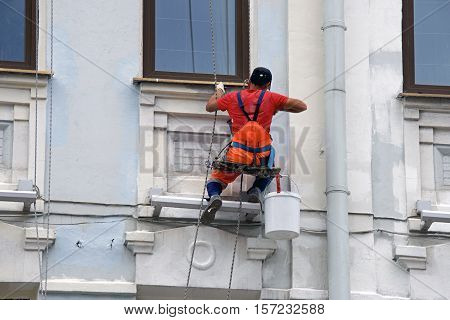 builder worker painting facade of high-rise building with rolle