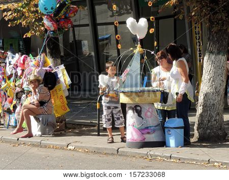 VORONEZH, RUSSIA - September 19, 2015: Elementary age boy buy cotton candy on the street stall near salesgirl with souvenir balloons and flags in the sidewalk of the city street during the celebration of the City Day. September 19, 2015 in Voronezh, Russi