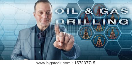 Happy business executive with a toothless smile is touching the phrase OIL & GAS DRILLING on a virtual control screen. Fossil fuel industry concept and technology metaphor for the petroleum market.