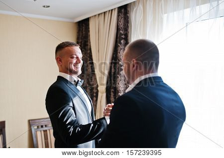 Two Handsome Male Friends Meet And Shaking Hands Each Other. Groomsman Or Best Man Greeting Groom At