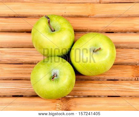 Organic granny smith apple on natural bamboo table