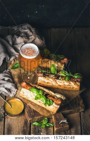 Glass of wheat unfiltered beer and homemade grilled sausage dogs in baguette with mustard, caramelised onion and herbs on serving board over rustic wooden background, selective focus, copy space
