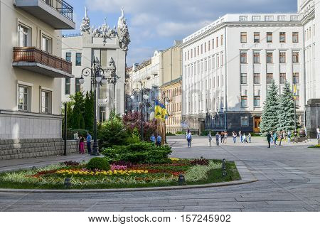 Kiev, Ukraine - May 25, 2013: Bankova street with several Ukrainian government buildings such as President's administration with flags and people walking