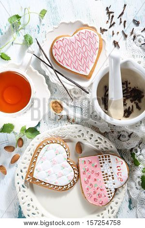 Gingerbreads in the form of hearts and tea are served on a table