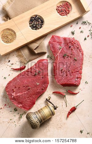 Piece of fresh beef and mill for spices lie on a table-top