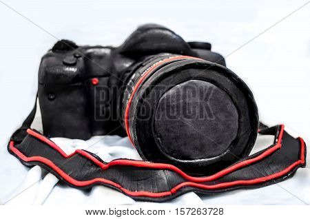 Cake in the form of a camera with a large lens on a light background