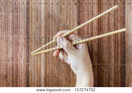 Chopsticks in a children hand. Food sticks. On a wooden background