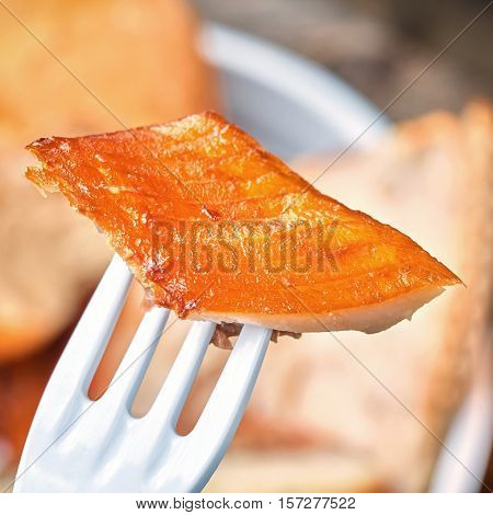 A piece of smoked fish on a fork