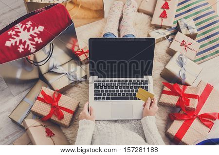 Christmas online shopping top view. Female buyer makes order on laptop with credit card, copy space on screen. Woman buy presents, prepare to xmas, among gift boxes and packages. Winter holidays sales