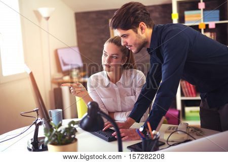Creative business colleagues using desktop computer in office