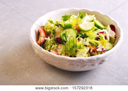 Bowl of fresh salad made of cucumber green leaves and tomato