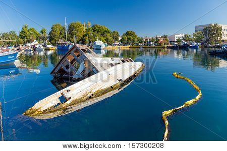 ELEUSIS, GREECE - NOVEMBER 18: Sunken boat in the harbor on November 18, 2016 in Eleusis. Eleusis is a town in West Attica, Greece and was named the European Capital of Culture for 2021.