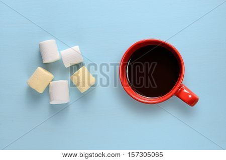 Marshmallow and coffee cup on blue table top view