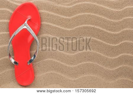 Pink flip flops with rhinestones on the wavy sand. With place for your text