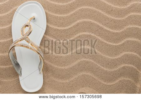 White flip flops with rhinestones on the wavy sand. With place for your text