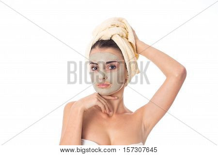 beautiful girl takes care her skin with cleansing mask on face and towel on head isolated on white background. Health care concept. Body care concept. Young woman with healthy skin.
