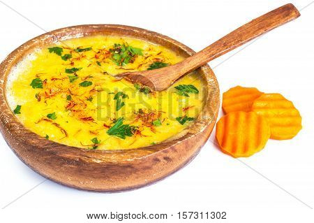 Pumpkin cream soup with saffron and parsley in a wooden bowl. Studio Photo