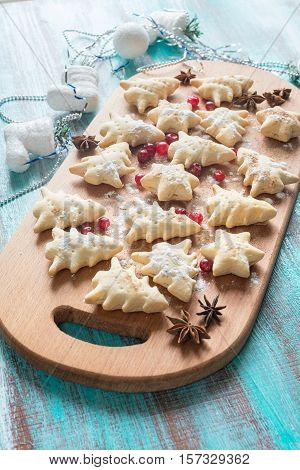Preparing for holidays. Festive cookies in the shape of Christmas trees and stars sprinkled with powdered sugar is lying on wooden table among cranberries spices and Christmas-tree decorations.