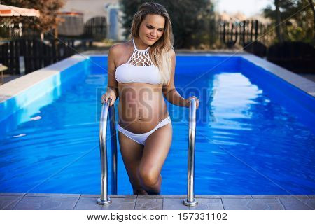 Beautiful Pregnant Woman Climbing Up From The Pool, Spending Summer Vacation On Luxury Resort, Happy