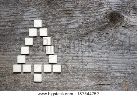 Christmas tree greeting card made of lump sugar on wooden background