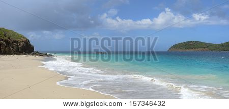 Panoramic of turquoise blue sea washing up sandy shore of Zoni Beach on Isla Culebra in Puerto Rico on sunny day