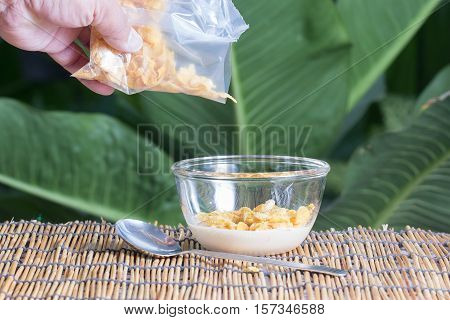 Hand putting cornflakes from bag to the cup
