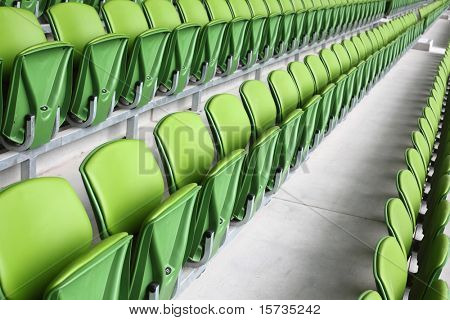 Rows of folded, green, plastic seats in very big, empty stadium