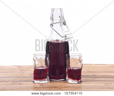 Homemade raspberry liqueur in clear glass bottle with swing top and shot glass on bamboo table