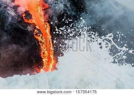 Waves washing up on molten lava flowing into Pacific Ocean on Big Island of Hawaii
