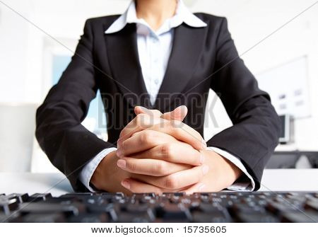 Photo of secretary with crossed fingers of both hands