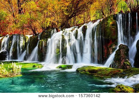 Waterfall And Azure Lake With Crystal Water Among Fall Woods