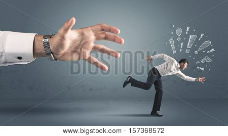 Business person with hand drawn exclamation marks getting away from a big hand concept on background