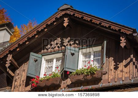 Wooden gable of typical Austrian rustic house with two windows shutters and flower boxes