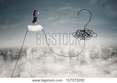 Businesswoman standing on the cloud while looking at a question mark and chaos symbol with binoculars