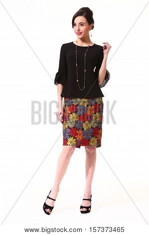 woman with updo hair style in cocktail party blac blouse patchwork skirt high heel shoes stand full body length isolated on white