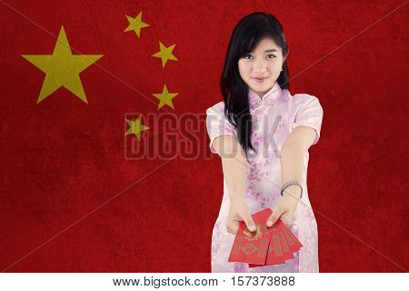 Image of pretty young woman wearing cheongsam clothes and showing red envelope with Chinese flag background