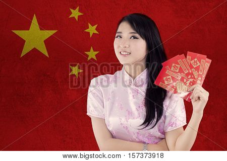 Image of attractive chinese girl wearing cheongsam clothes and holding red envelope in front of a national China flag