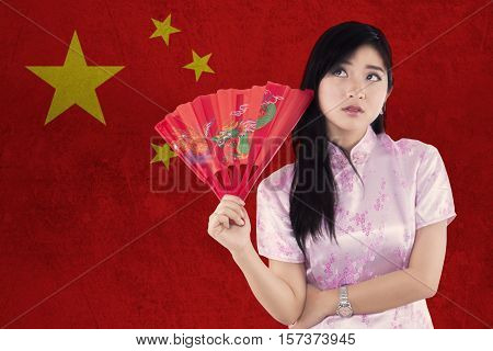 Portrait of thoughtful Chinese woman wearing cheongsam dress while holding a fan and thinking idea with Chinese flag background