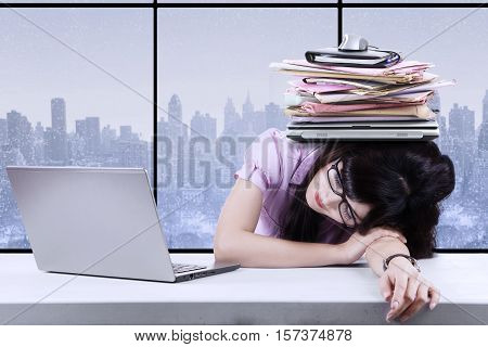 Image of pretty female entrepreneur sleeping with burdens on her head while overworking in the office