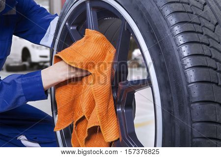 Close up of a male mechanic hand holding a microfiber cloth while cleaning car tires and wheels in the workshop