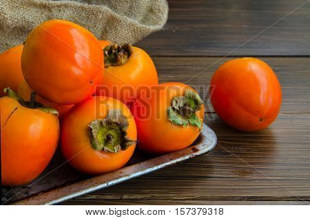 Fresh organic persimmon in vintage metal plate on rustic wood background. Concept for healthy food vegan or raw diet.