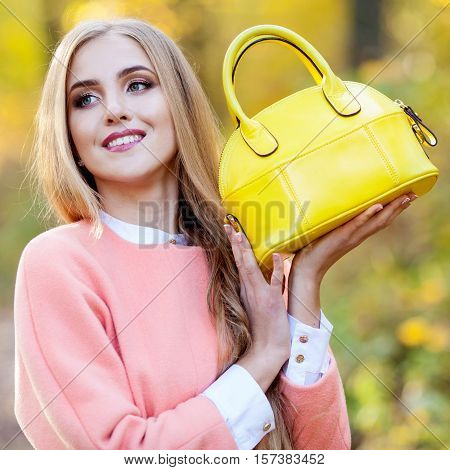 Portrait of a beautiful girl with long hair in a coat holding a yellow bag fashion autumn day in the park
